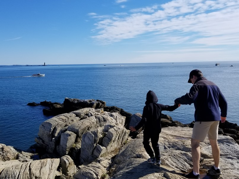 Father and son hiking on rocks in Fort Williams, Cape Elizabeth, Maine