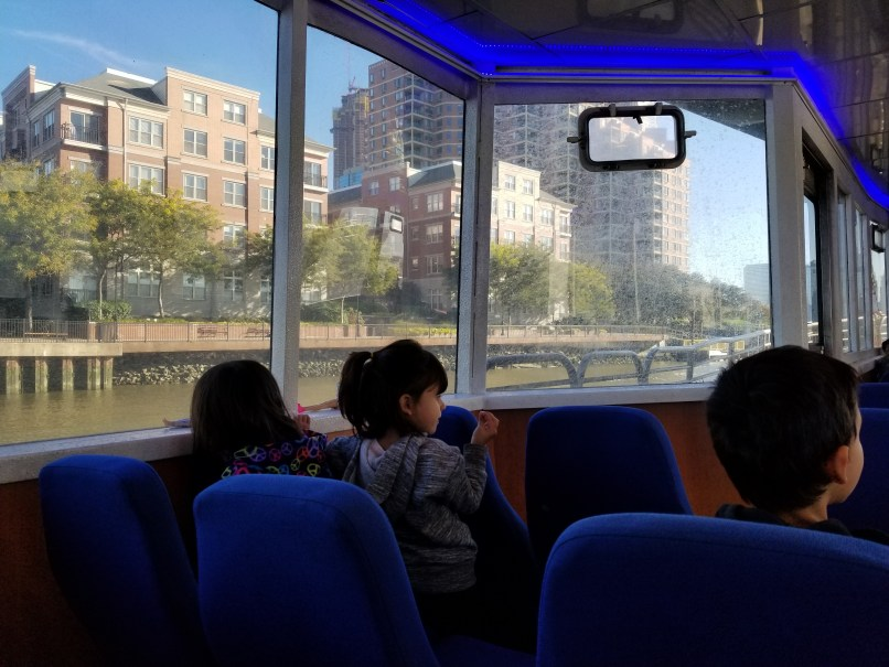 Two young girls and a boy look out the window of the NY Waterway ferry at Jersey City.