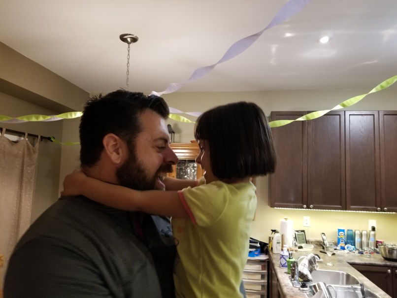 Uncle holding his 4-year-old niece, whos s marvelling at his beard.