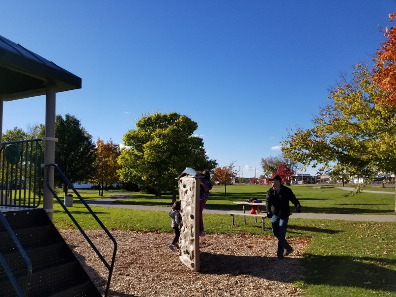 A 4-year-old girl and an 8-year-old girl climbing a movable rock climbing wall at a playground. The father is standing beside the wall, watching the children.