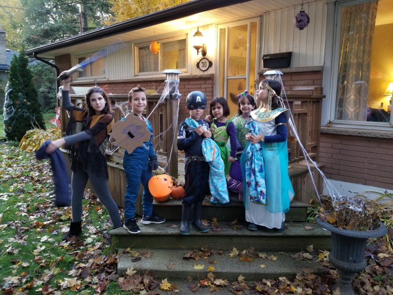 Group of children wearing Halloween costumes. One girl is dressed as a jedi, two boys as superheroes, a young girl is dressed as Tinkerbell, and another girl is dressed as Cleopatra.