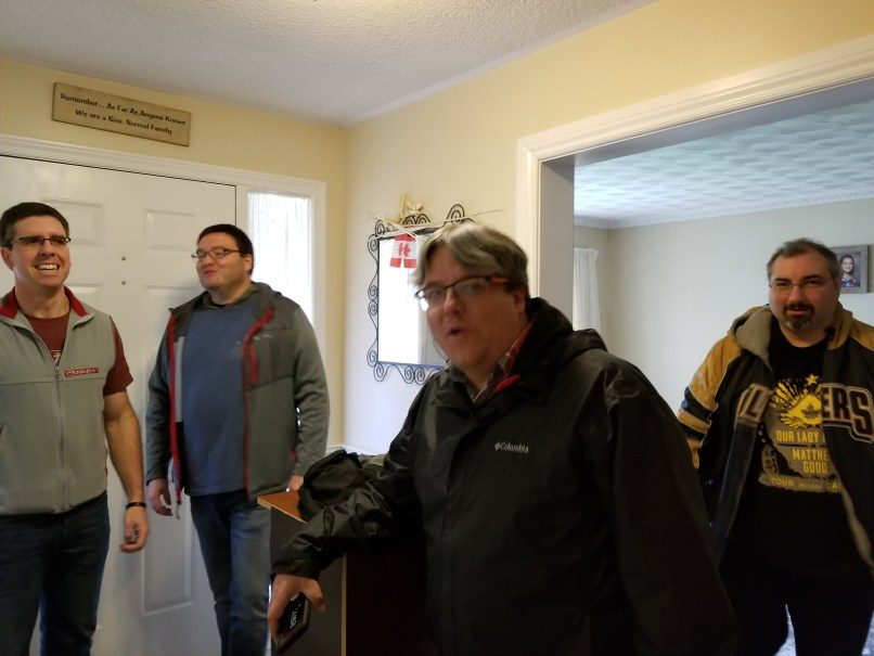 4 Men standing in front of a door. They are getting ready for a night out