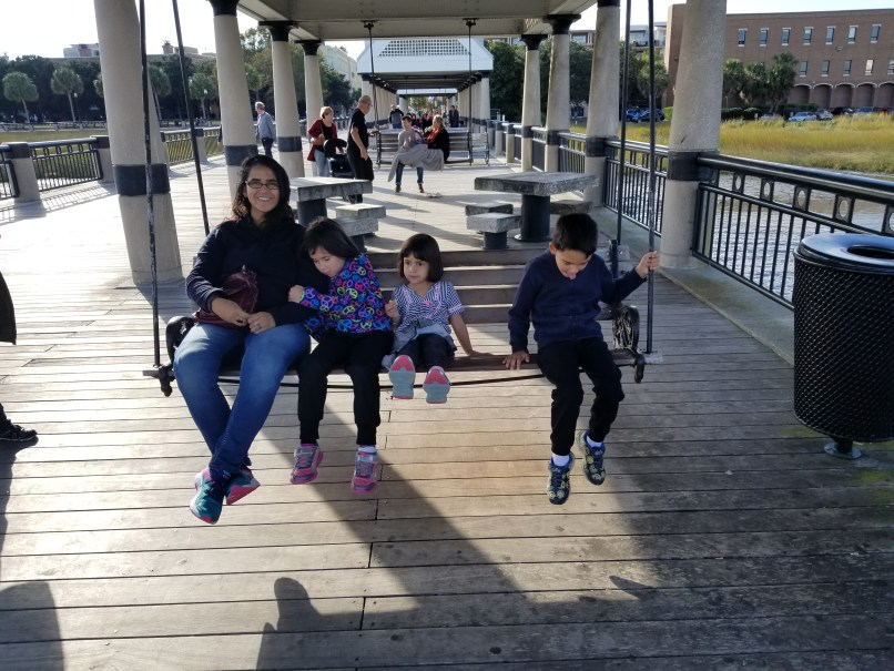 Mother, two young daughters and a young son sitting on a swing in Charleston, South Carolina