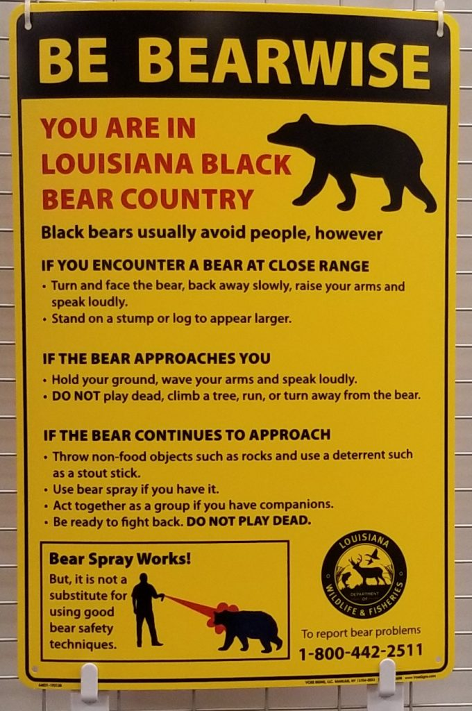 """Be Bear Wise"" sign at Slidell Public Library. Sign states that if you encounter a bear at close range, you should face the bear and back away slowly while raising your arms and speaking loudly. If the bear approaches, throw rocks at it or use bear spray if you have it."
