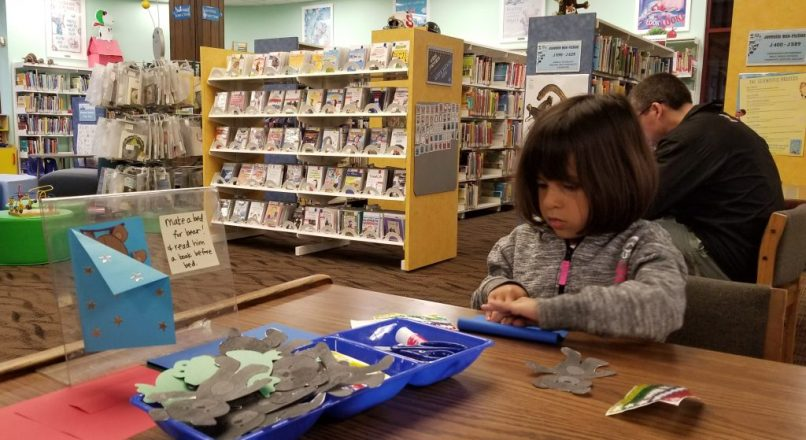 Girl making a craft in the junior section of the Slidell Public Library