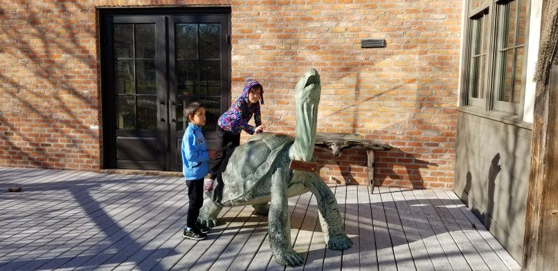 A boy and a girl climb the tortoise sculpture at the Atchafalaya Visitor Center in Louisiana