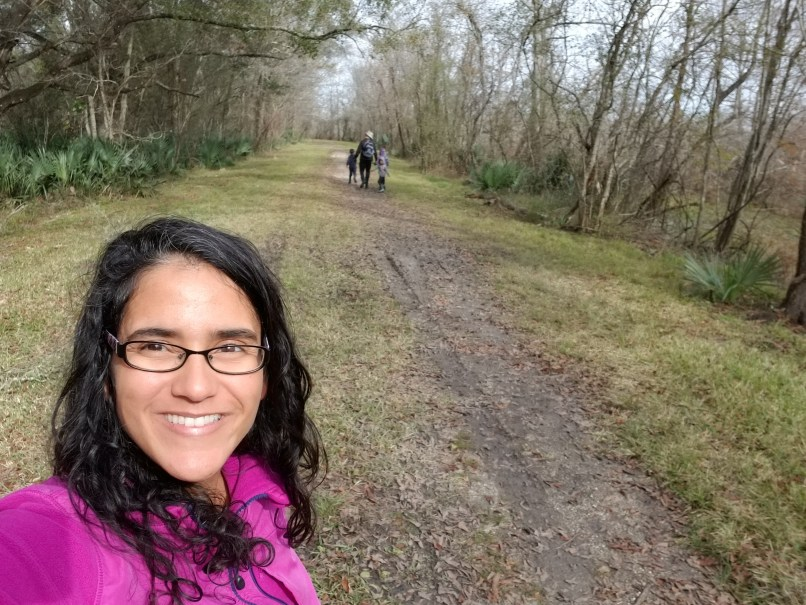 Cypress Island Preserve. Woman takes a selfie, with man and children walking in the background in the forest.