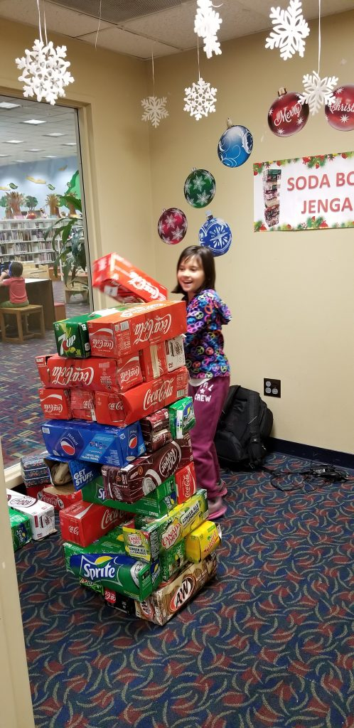 """A girl plays """"soda box jenga"""" at Sterling Public Library in Baytown, Texas"""
