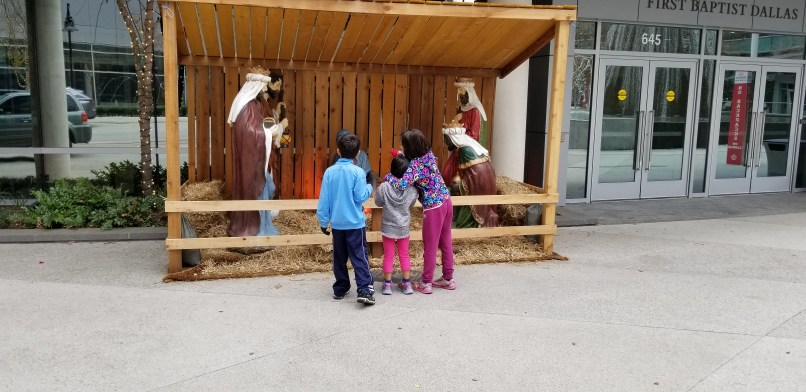 A 6-year-old boy, a 4-year-old girl, and an 8-year-old girl stand in front of a nativity scene. The older girl is pointing her finger at the display while she has her other arm around her younger sister.