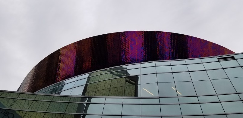 The top of the First Baptist Church building in Dallas. A purple mirrored accent stands atop a glass-sided building.