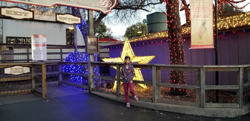 An 8-year-old girl standing in front of a star Christmas decoration at Six Flags Over Texas.