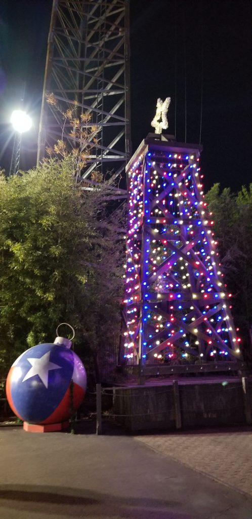 A Texas flag ornament and small lit-up tower at Six Flags Over Texas Holiday in the Park.