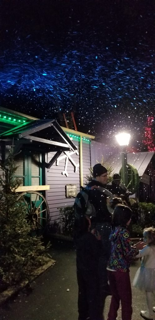 A father holds a small child while an older child catches snow flakes at Six Flags Over Texas. The snow flakes are really soap bubbles.