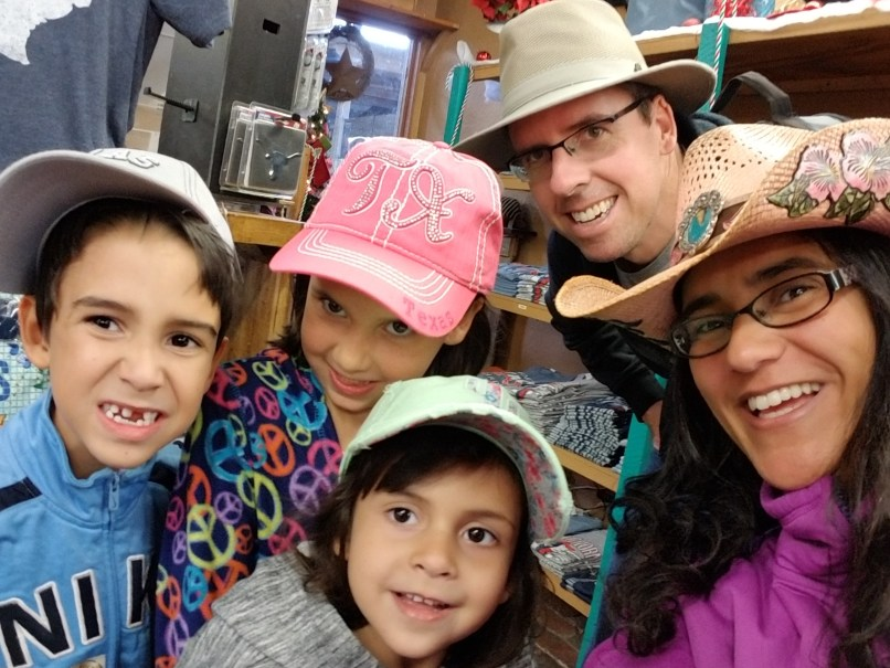 Father, mother, and three young children wearing hats in Longhorn Store, Fort Worth, Texas