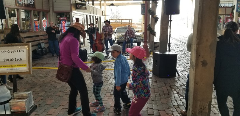 Mother and children dancing in front of a band in Fort Worth Stockyards, Texas