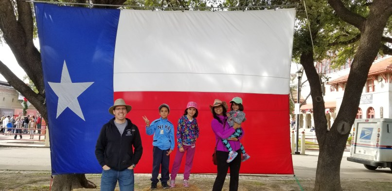 Family in front of Texas Flag in Fort Worth, Texas. Father, son, daughter, and mother holding youngest daughter.