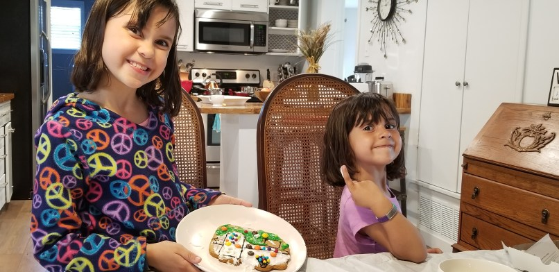 Two girls show a gingerbread camper.