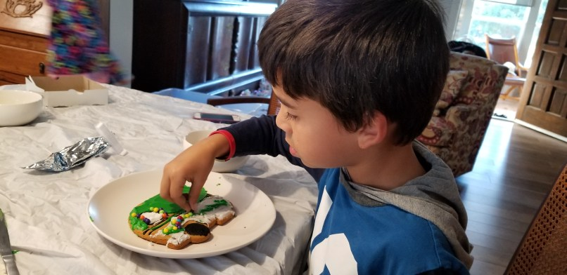 boy decorating gingerbread house in airbnb in Granbury, Texas