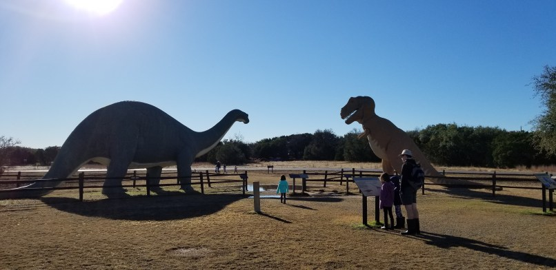 A father, son, and daughter read a panel while a younger daughter walks towards two life-size dinosaur sculptures. Dinosaur Valley State Park, Texas