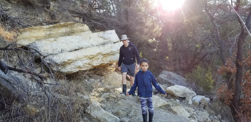 Father and 6-year-old son walking in Dinosaur Valley State Park Dinosaur Footprint Trail