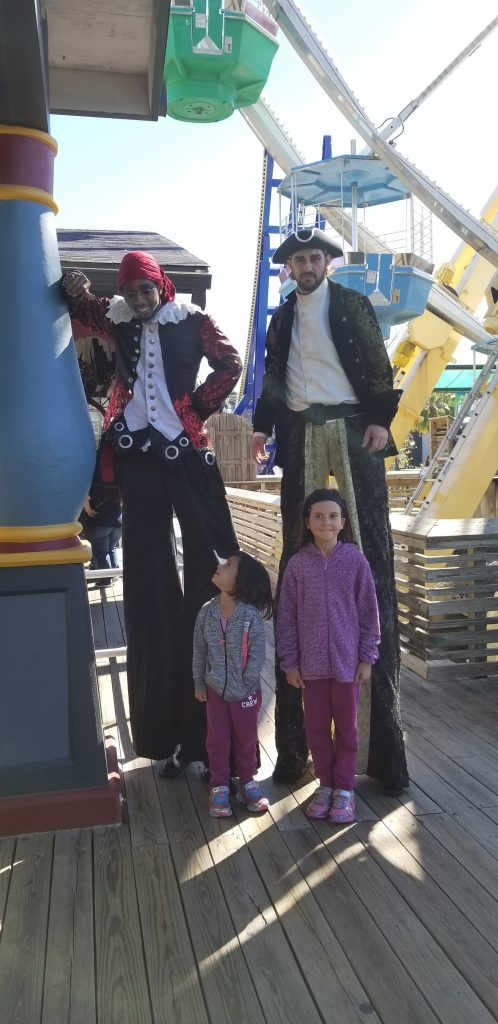 two young girls pose with pirates on stilts at Six Flags Fiesta Texas
