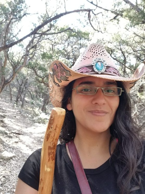 Mariana wearing a cowboy hat and holding a wooden walking stick at Bridges trail, Garner State Park, Texas