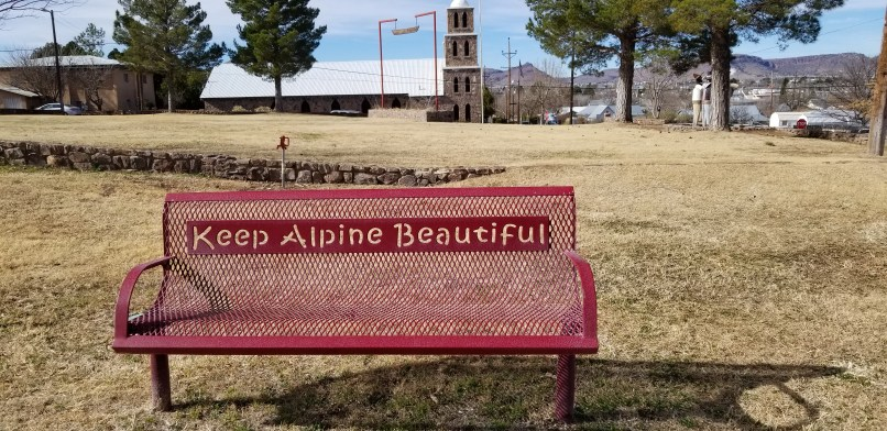 """A red bench has the words """"Keep Alpine Beautiful cut out on the metal. Behind the bench, a church is visible in the distance."""