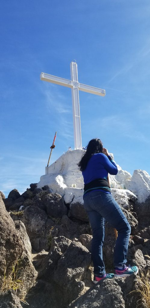 A woman looks at a cross on a hill. She is leaning on a wooden walking stick.