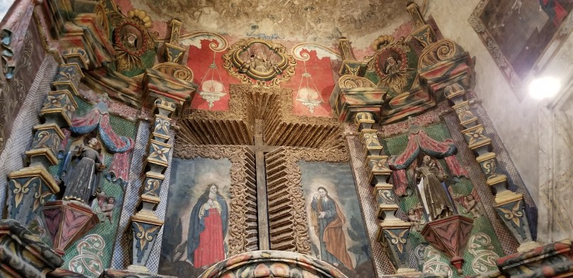 San Xavier del Bac Mission church. A cross is etched into a wall and surrounded by paintings of saints.