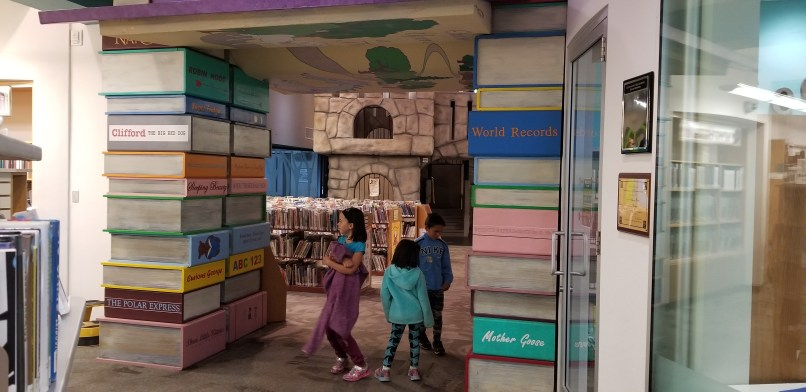 Two girls and one boy stand under the archway into the children's area of the Apache Junction Library. The archway is made of representations of children's books.
