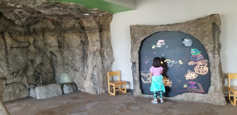 4-year-old girl is seen from the back playing at the dragon's den of the Apache Junction library.