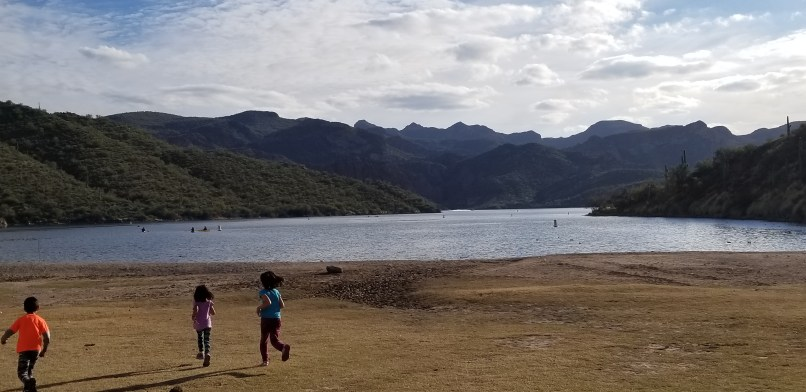 A 6-year-old boy, a 4-year-old girl, and a 9-year-old girl run towards Saguaro Lake in Tonto National Forest. Mountains can be seeing behind and on each side of the lake.