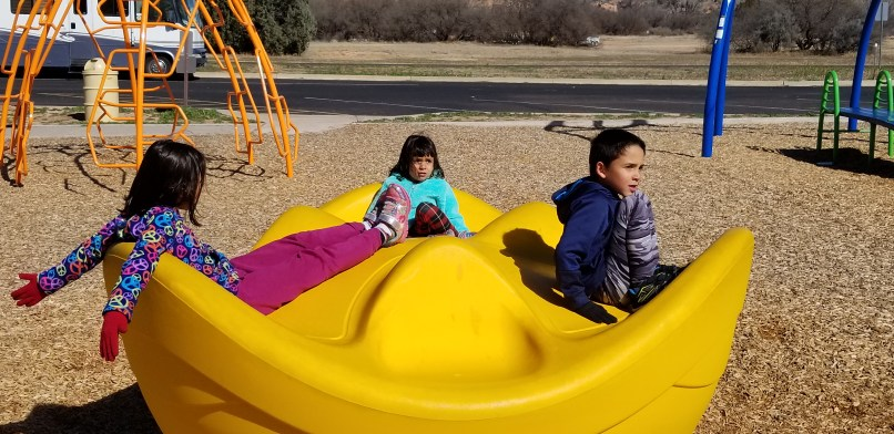 A 9-year-old girl, a 4-year-old girl, and a 6-year-old boy sitting on a yellow round-about type of playground equipment.