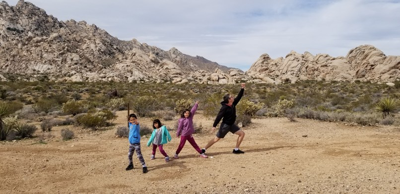 father and three children posing in front of mountains at the mojave national preserve
