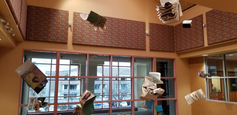 """flying books"" at Rancho Cucamonga Library, California. Books hang from wire, and pages have been arranged so that they look like they're flying off the books."