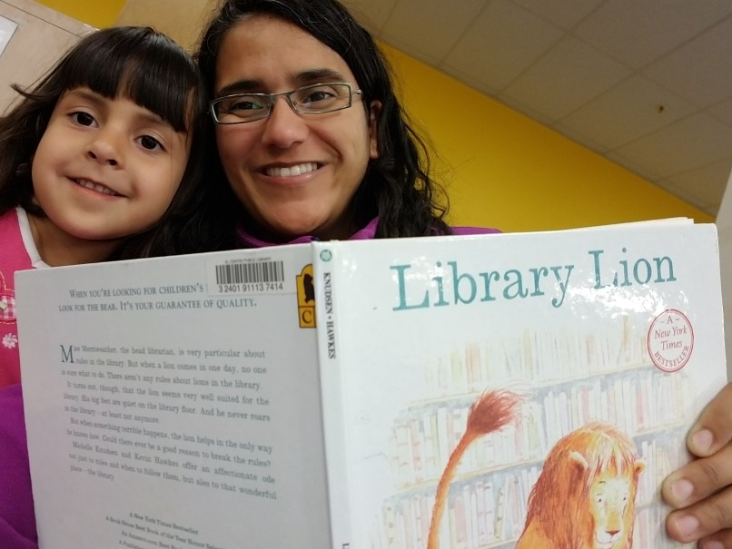 A mother and 4-year-old daughter hold up a copy of Library Lion.