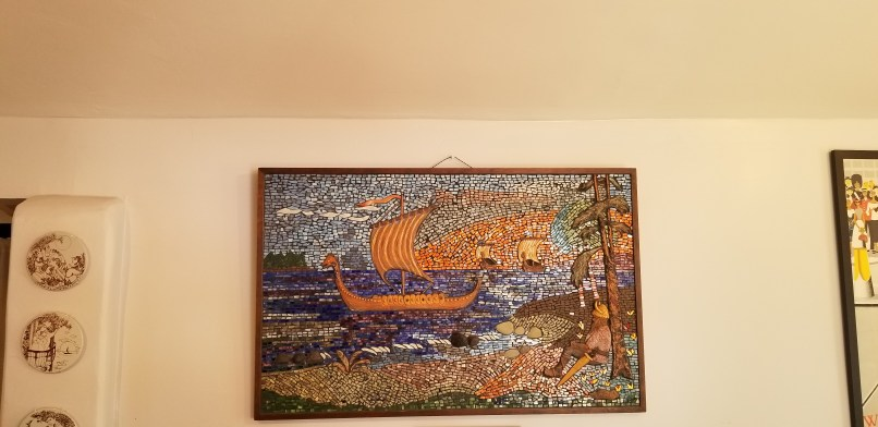 Mosaic picture of a viking ship on the ocean near the shore. using gold, blue, green, and brown tiles.