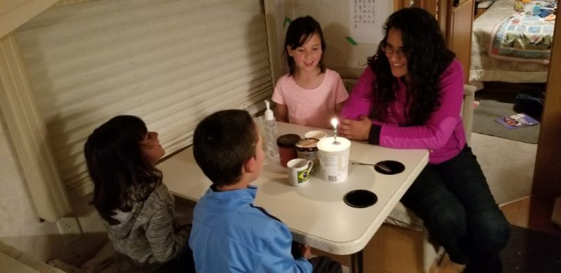 Mother, 9-year-old daughter, 4-year-old daughter, and 6-year-old son sitting around an RV dining room table. At the center of the table is an ice cream container with a lit birthday candle in it, beside a cup with a Brazilian flag.