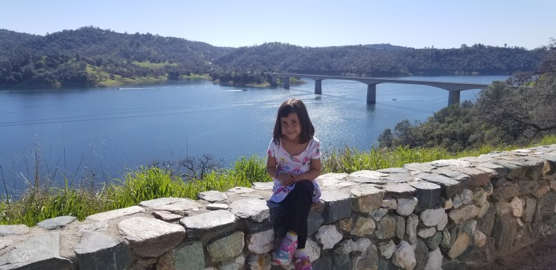 4-year-old girl sitting on rock wall at Carson Hill lookout. A bridge and a lake are behind her.