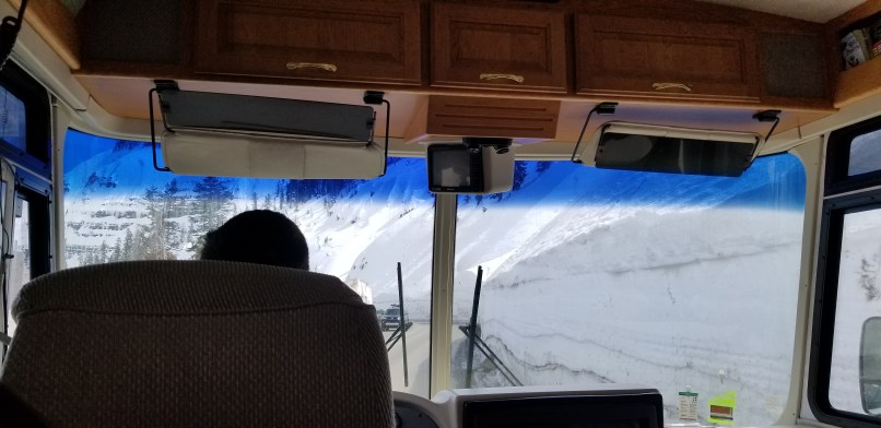 A large wall of snow as seen from the inside of an RV dashboard.
