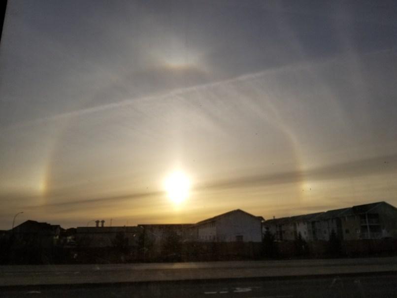rainbow around the sun behind some houses somewhere between Moose Jaw and Regina, Saskatchewan