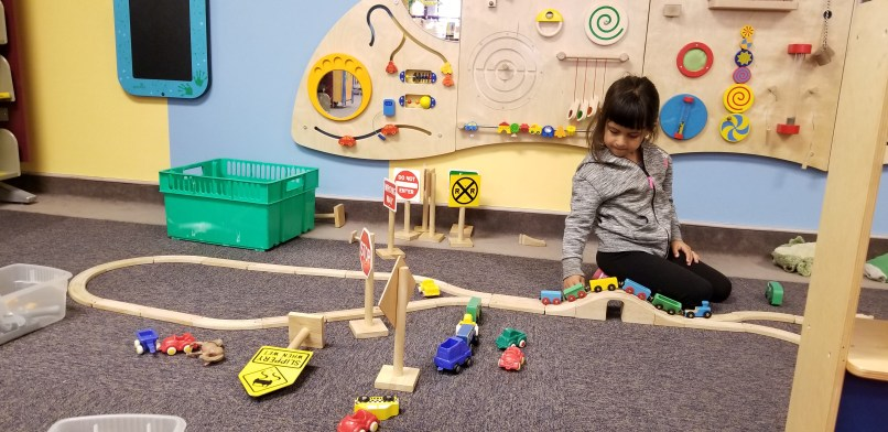 A 4-year-old girl plays with a train in the childrens area of Great Falls Public Library