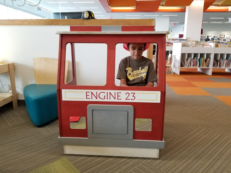 A 6-year-old boy wearing a toy firefighting hat plays behind a toy fire engine at the Quarry Park branch of the Calgary Public Library