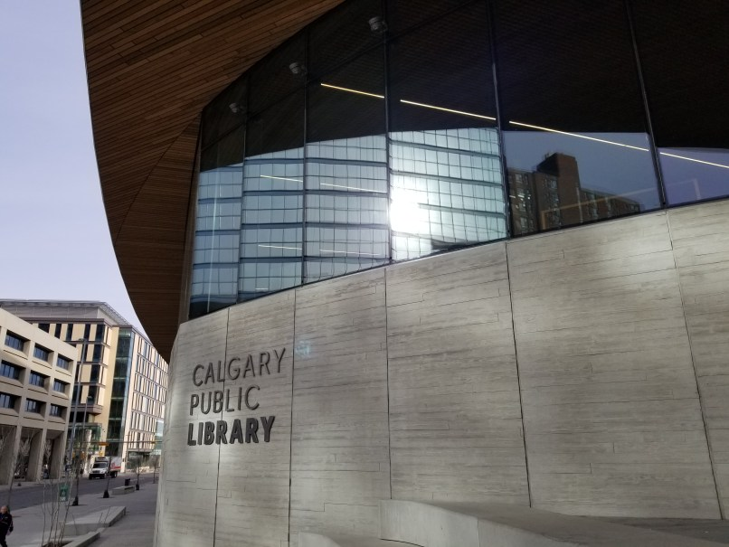 """The facade of the Calgary Central Library. The words """"Calgary Public Library"""" are seen below glass windows."""