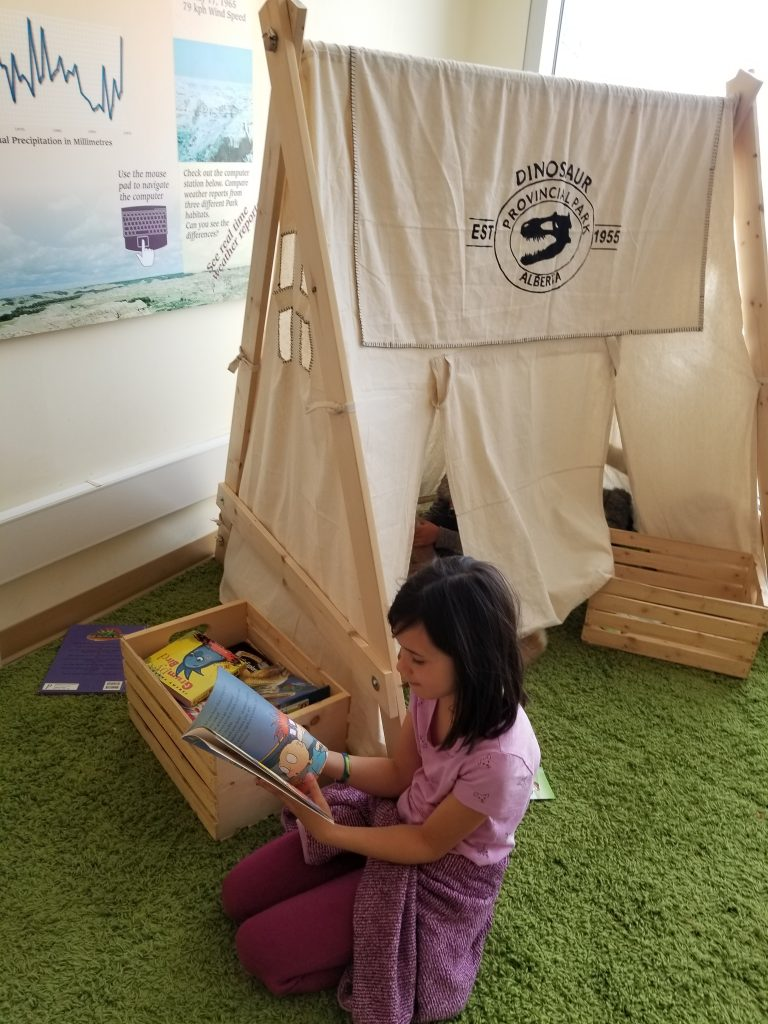 A 9-year-old girl reads a book while kneeling beside a play tent at the Dinosaur Provincial Park Visitor Center