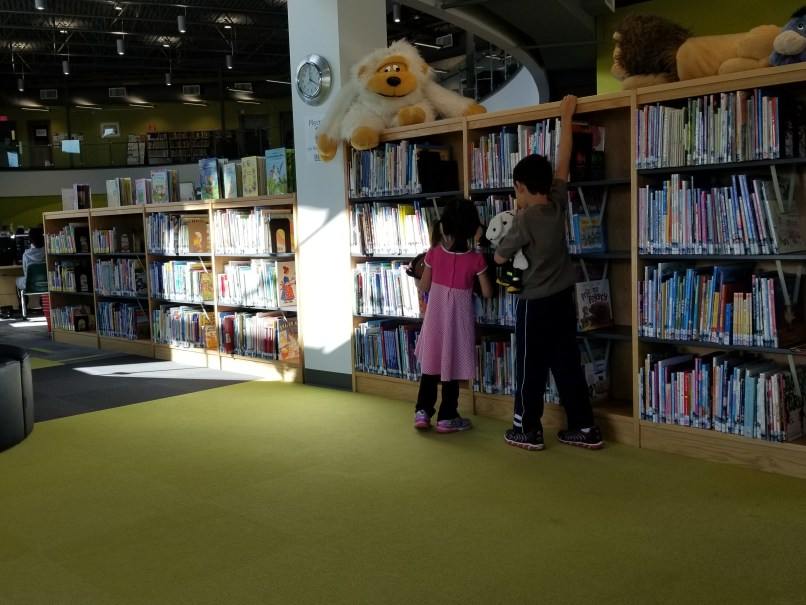 a 4-year-old girl and 6-year-old boy look at books on a shelf at the Brooks, Alberta library. The boy is holding a stuffed animal.