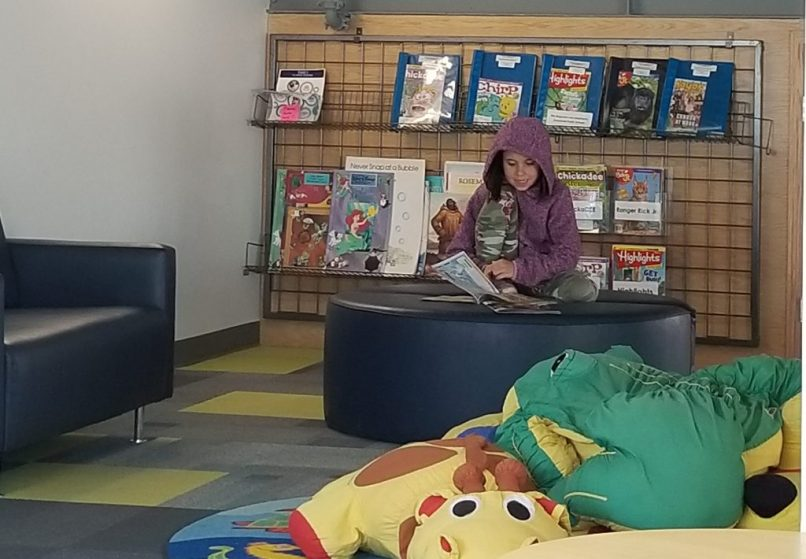A 9-year-old girl, wearing a pink hoodie, reads a book in the children's area of the Brooks, Alberta library.