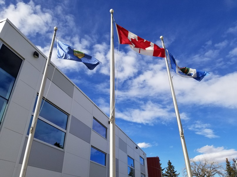 Three flags flying in front of a building in Brooks, Alberta