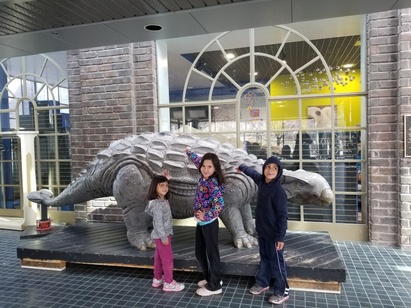 Three children pose with a dinosaur statue at the Saskatchewan Science Centre in Regina, Saskatchewan