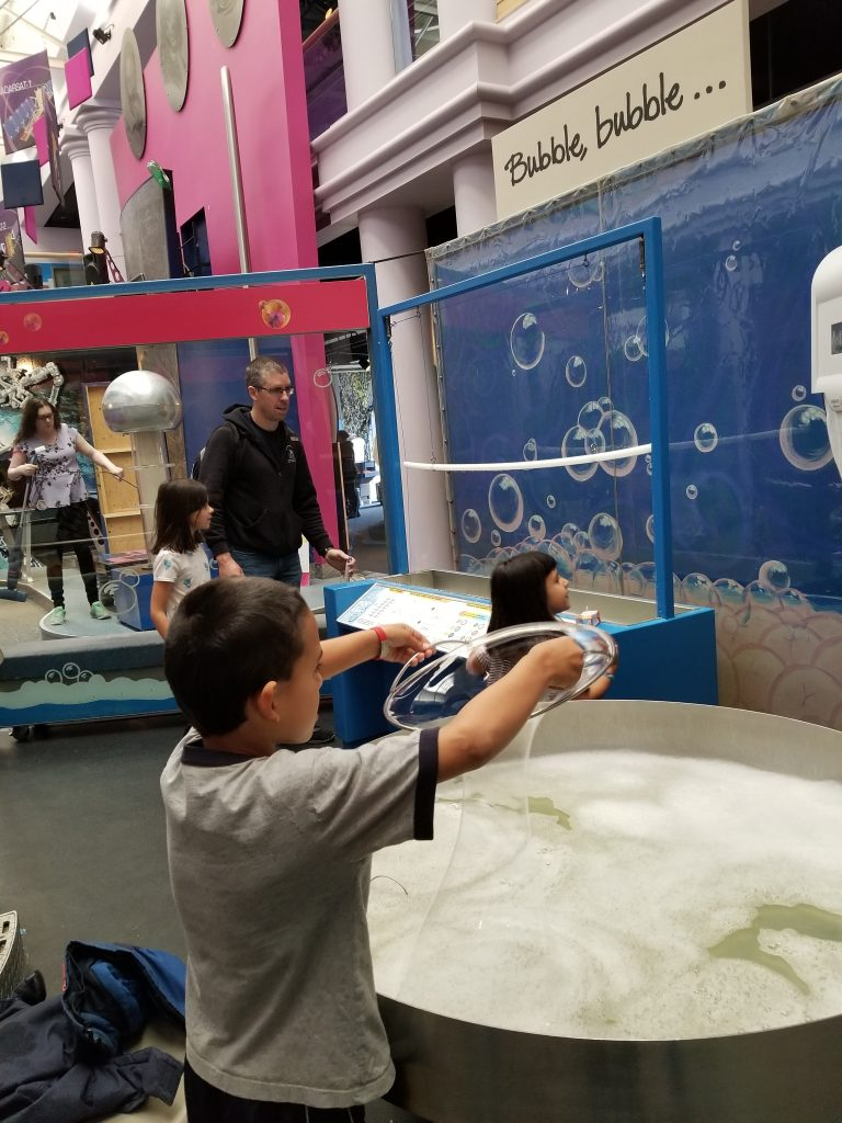 6-year-old boy making a bubble with a bubble ring at the Saskatchwean Science Centre